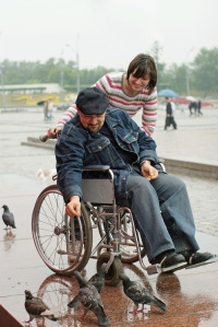 Woman and man on a wheelchair feeds birds in park